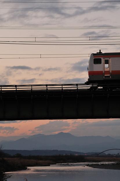 暮れ行く多摩川橋梁を渡るE233系快速電車