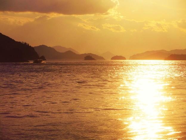 新春の夕陽の海を高速艇が走る。
