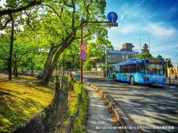 緑いっぱいのお城の横を走り抜ける空色のバス。