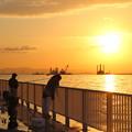 写真: 朝陽と釣り人